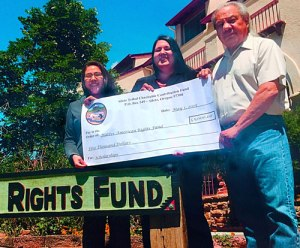 Alayna Farris, Whitney Gravelle, and John Echohawk recognize the donation from the Confederated Tribes of Siletz