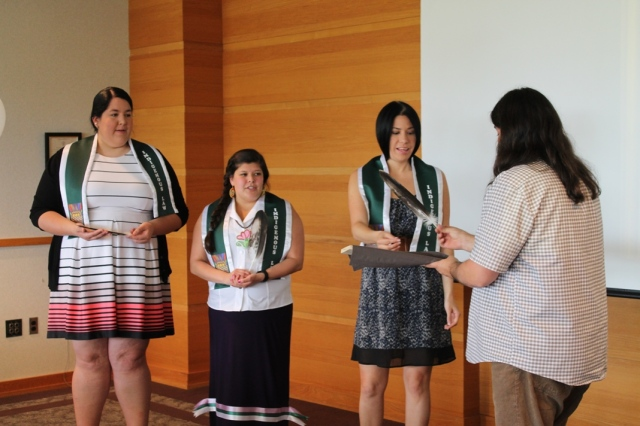 Professor Matthew Fletcher presenting the Native graduates with eagle feathers.